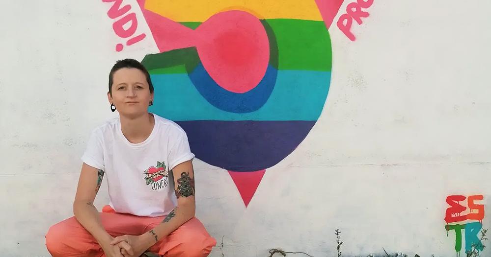 Irish queer street artist Emma Blake posing in front of one of her murals