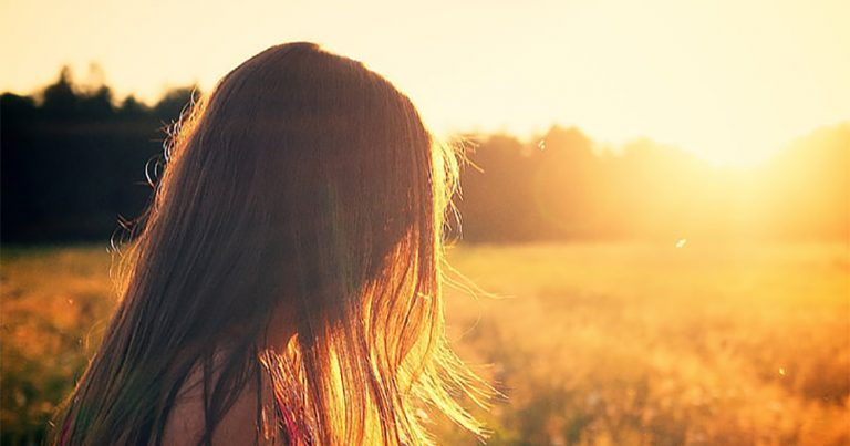 A woman with long hair covering her face in a field at sunset