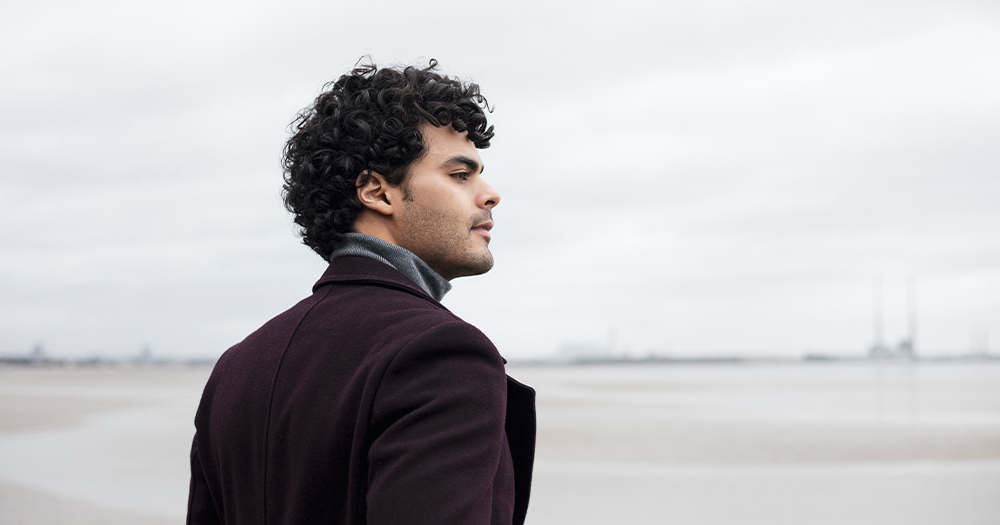A curly haired Brazilian man in a coat stands on a grey beach