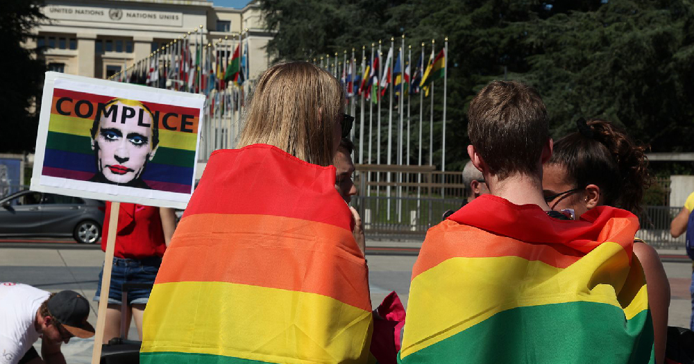 LGBT+ rights Russia two people wearing rainbow flags with a poster of Putin wearing making reading 'Complice'