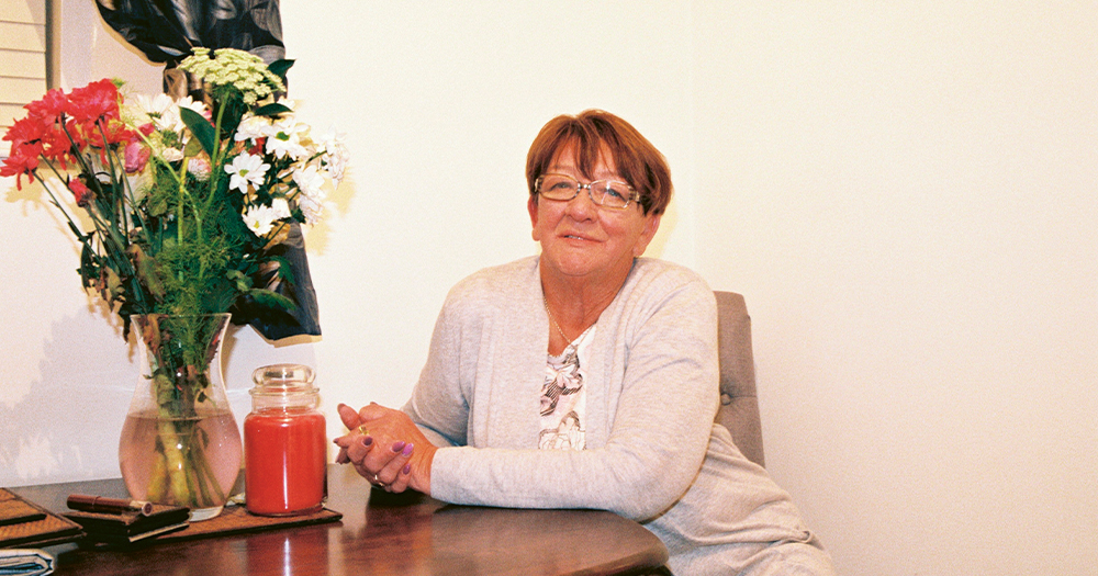 A smiling older woman wearing glasses sits at a table, a vase of flowers beside her