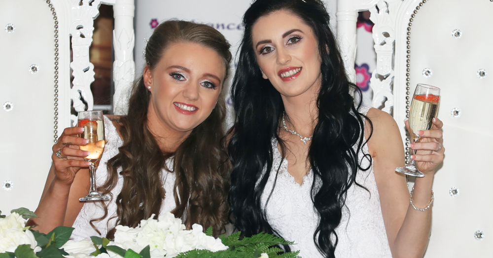 First same-sex couple married in Northern Ireland on their wedding day, they are both wearing white dresses and holding up glasses