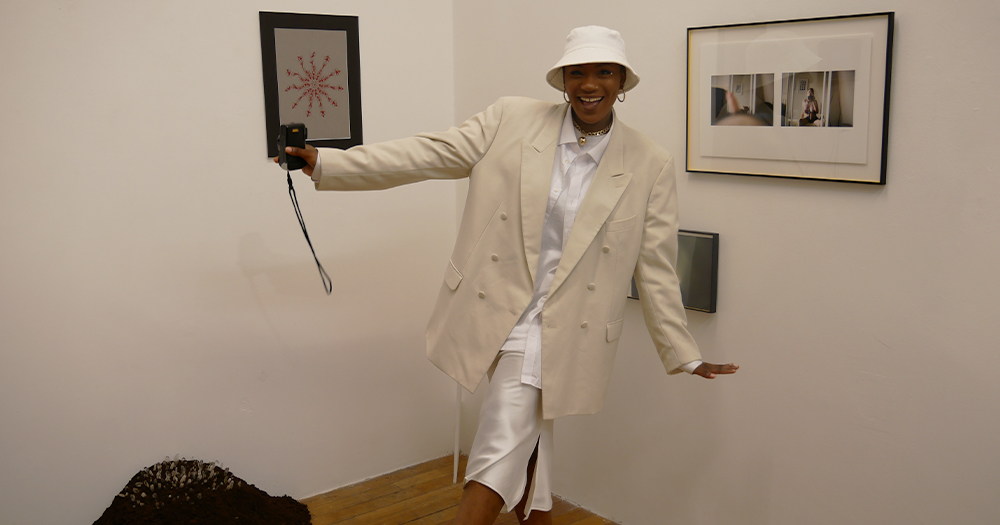 A woman holding a camera wearing a hat poses joyfully in an art gallery