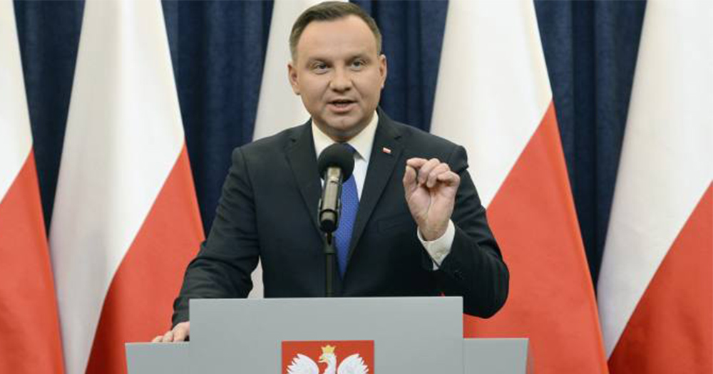 The Polish President Andrzej Duda, a middle aged man in a suit, speaks at a podium in front of Polish flags