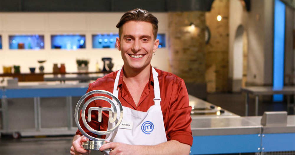 A smiling young man in a kitchen holding a trophy