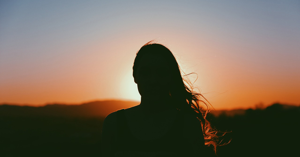 A woman stands silhouetted by the sunset