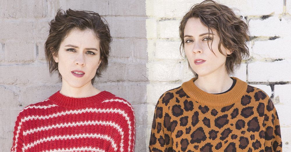 Tegan and Sara, two identical twin women wearing patterned jumpers and standing in front of a plain wall