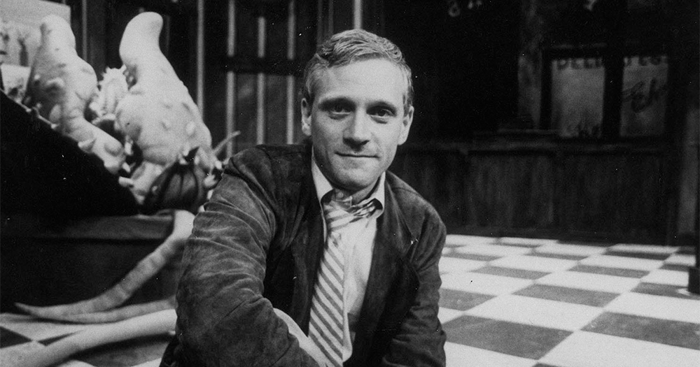 Howard Ashman, a young man, sits on the edge of a stage, a prop monster plant in the background