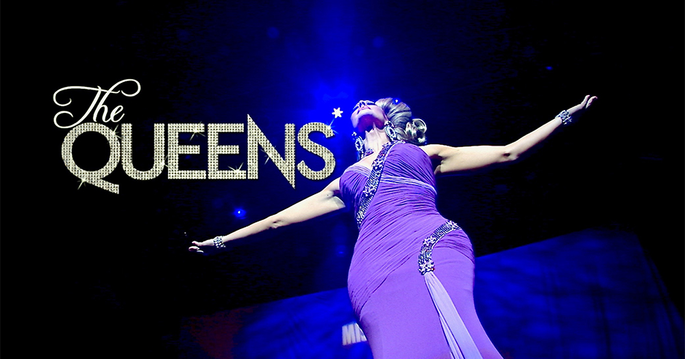 The Queens in big text beside a drag queen inn a long dress looking up into the air
