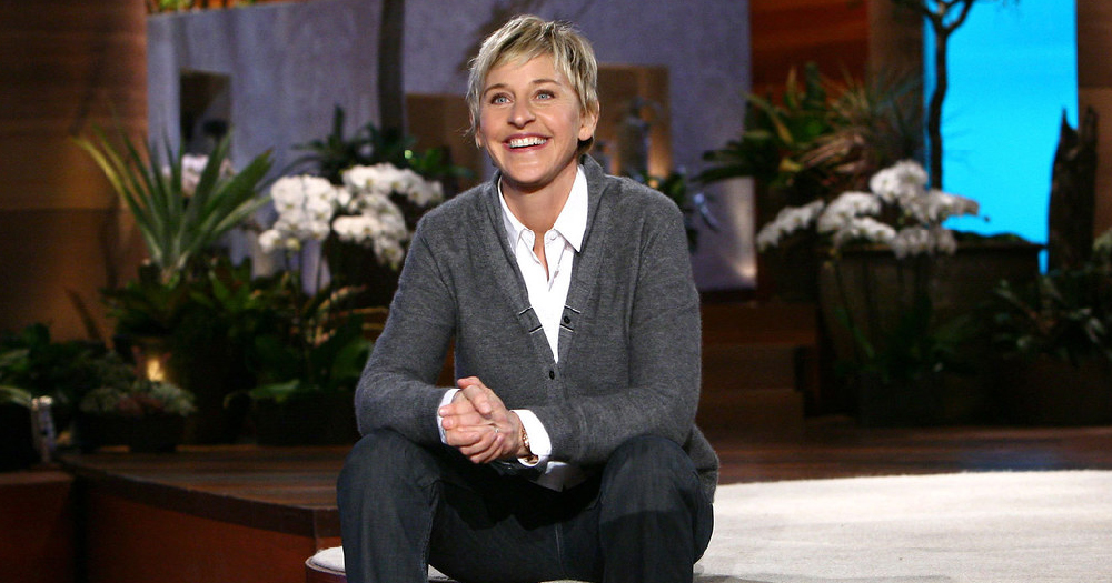 Ellen DeGeneres sits on the steps on the Ellen Show set