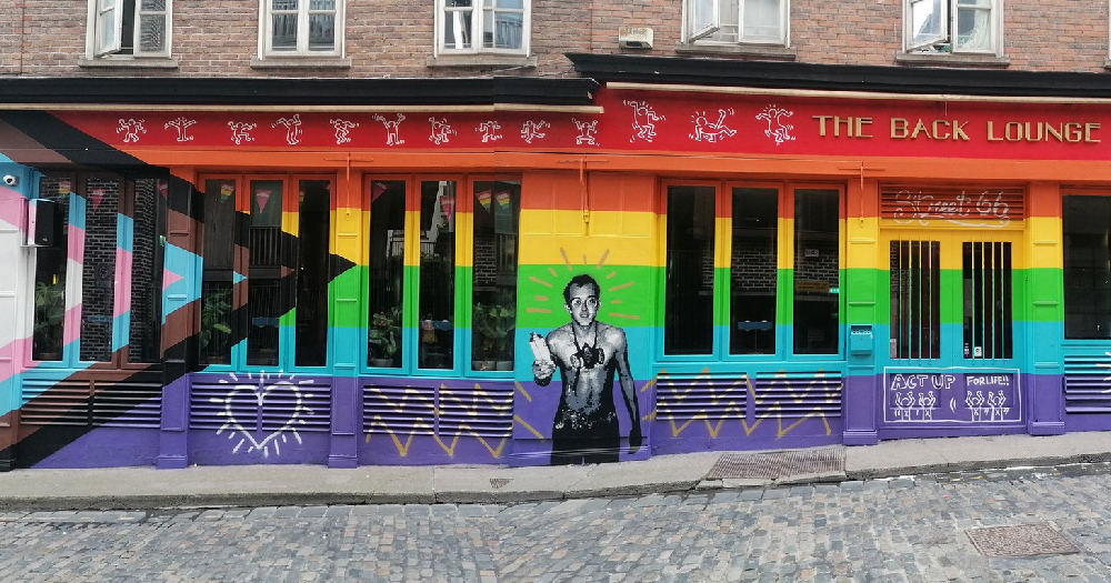 image of pub front Street 66 painted in the progress rainbow flag with a portrait of Keith Haring