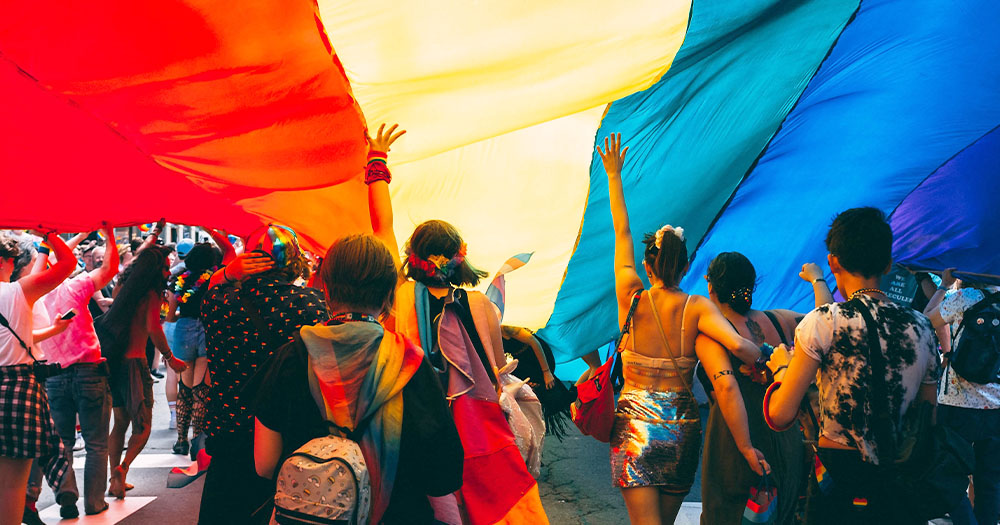 A large group of young people walking underneath a huge rainbow flag