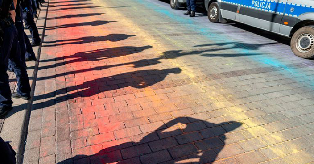 minister poland the shadow of police officers covers what is left of a road covered in chalk paint creating a rainbow flag