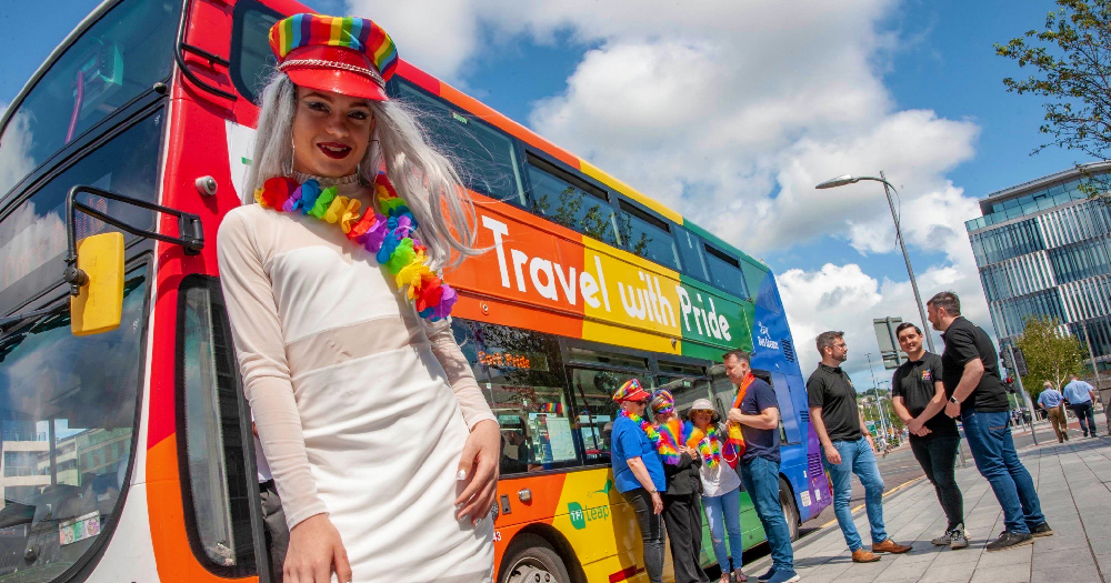 Youngest drag queen Instagram Kara O'Hara stands in front of a bus coverd in the the rainbow flag