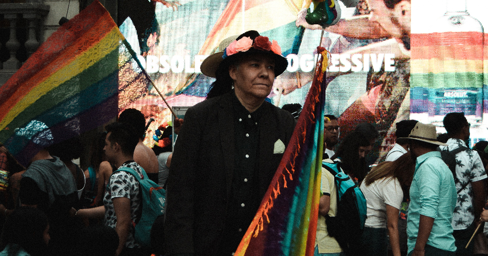 an LGBT+ person holds a felt rainbow flag in Paseo de la Reforma, Mexico City, México