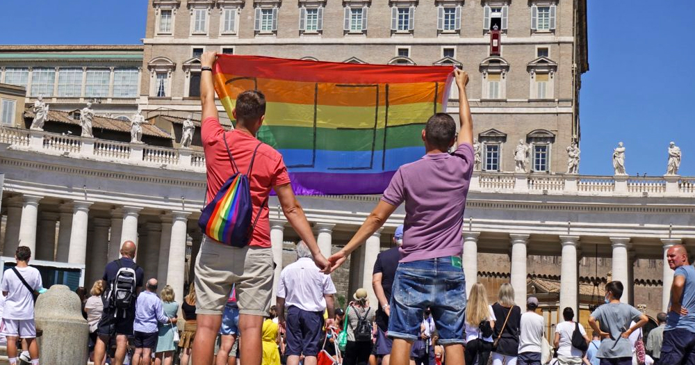 Two gay Polish men holding hands and lifting a pride flag in the air in the Vatican