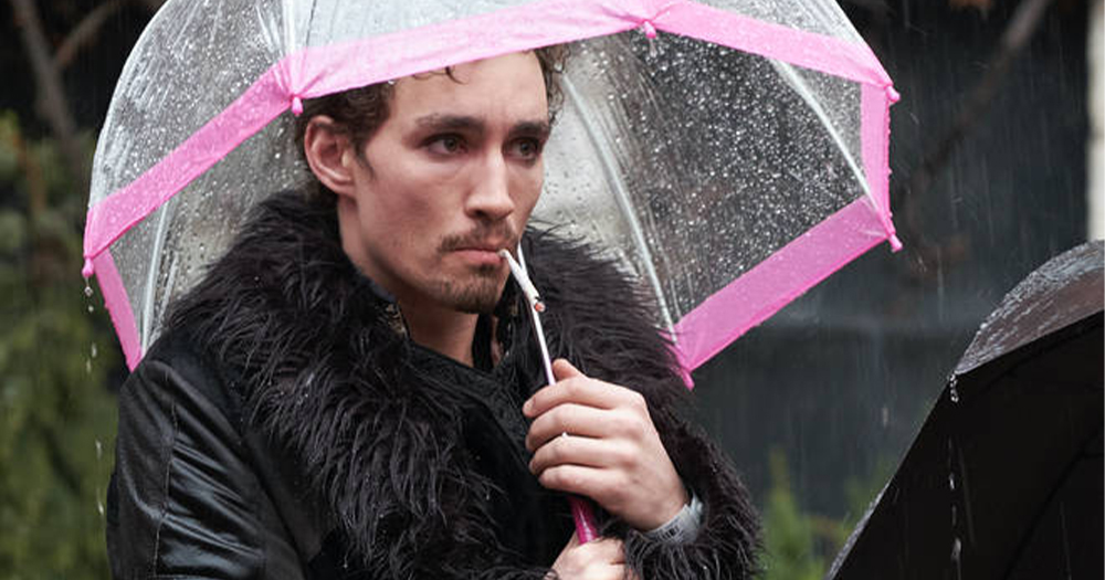 A punky guy in a black fur coat smokes while holding a plastic umbrella