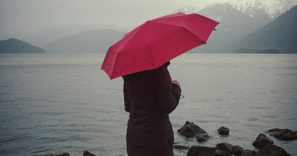 A person holding a red umbrella by the sea, the red umbrella has become a symbol for SWAI who recently denied emergency funding