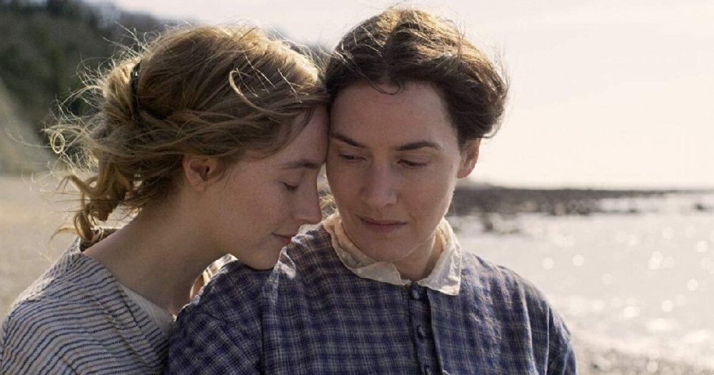 still from Ammonite trailer which has lesbian twitter talking. Pictured is Saoirse Ronan resting her chin on Kate Winslet's shoulder on a beach
