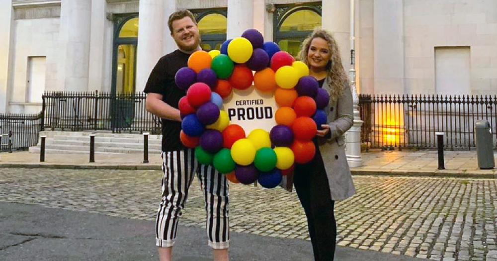 a masculine presenting person and a feminine presenting person stand holding a balloon garland with the certified proud logo in the centre