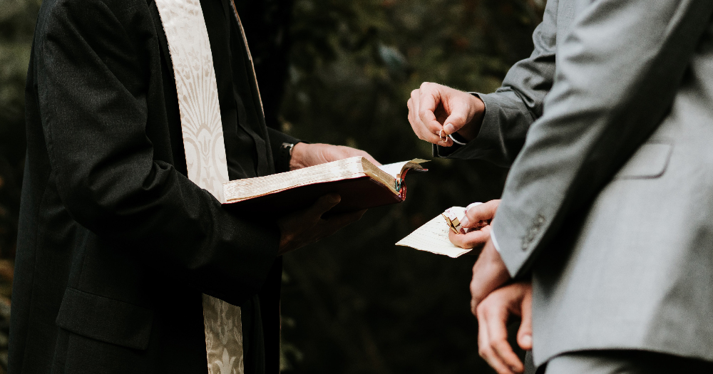 same sex religious weddings a religious offiator holds a bible as two men wearing suits hold rings on top of the bible