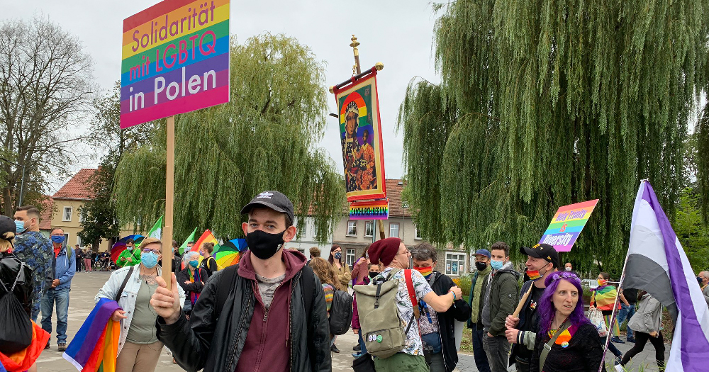 A group of people carrying LGBT+ banners