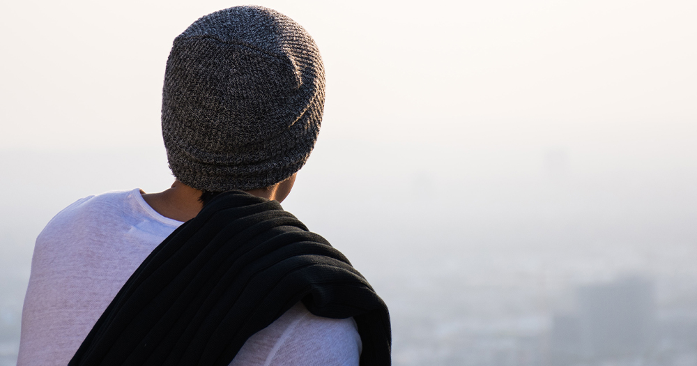 A person on a hill looks out over a distant city