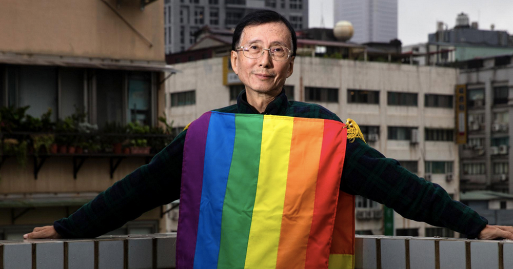 An older Asian man on a balcony draped in a rainbow flag