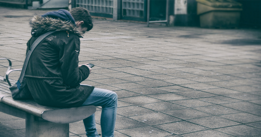 A teenager looks at his phone while sitting on a bench