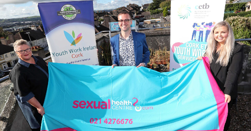 Sexual Health Centre members of the sexual health center and youth work ireland cork hold a banner which says 'sexualhealthcentre.com'