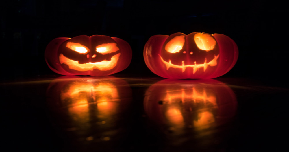 Halloween is not cancelled Two smiling jack-o-lanterns lit up in the dark