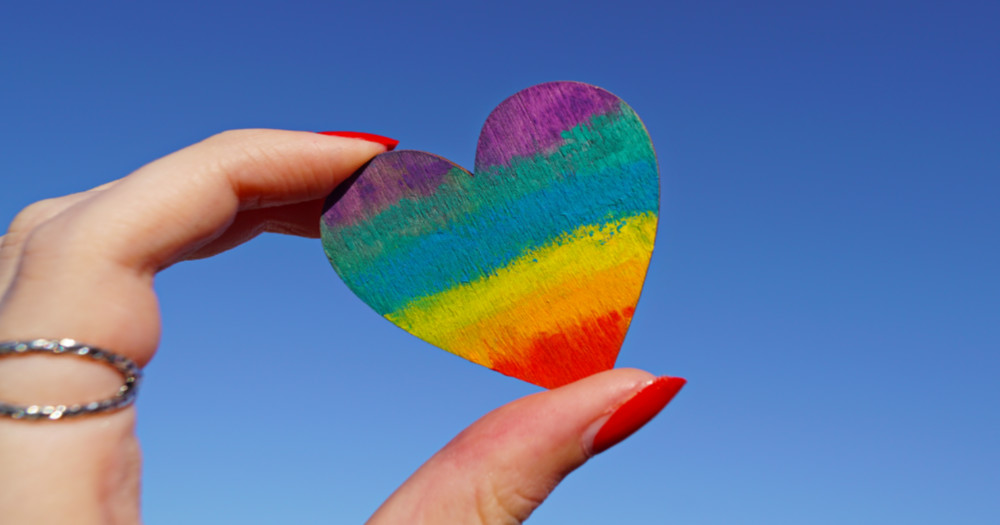 Fingers holding up a rainbow heart