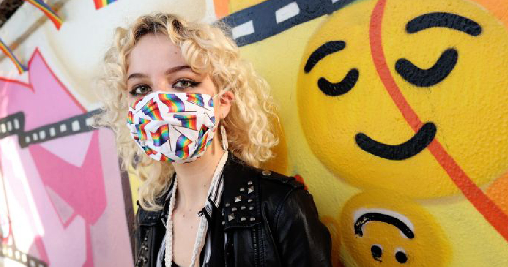 Live Out Loud launch photo Feminine person stands in front of a mural with happy face emoji. They have shoulder length blonde wavy hair and are wearing a facemask covered in rainbow flags.