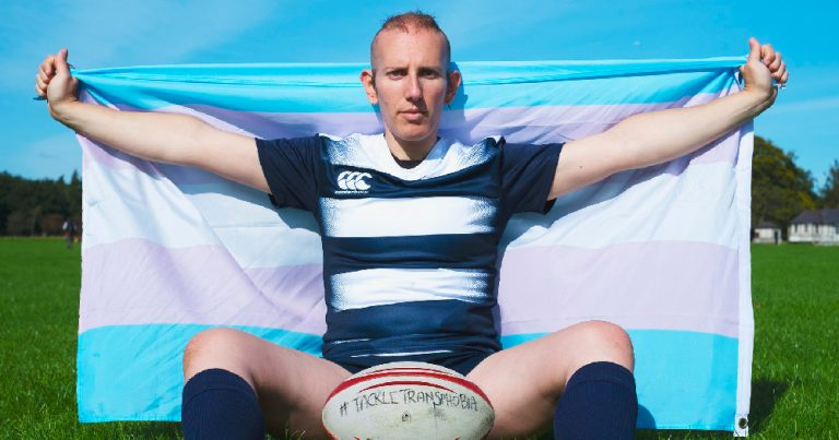 World Rugby. A trans woman sits on a rugby pitch wearing a rugby jersey and holding a trans flag behind her