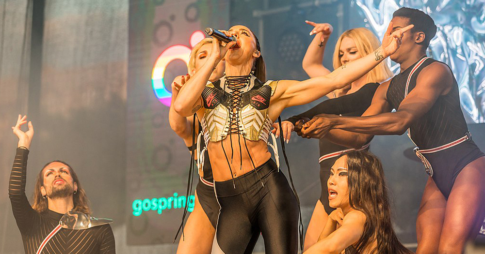 A female singer surrounded by female dancers on stage