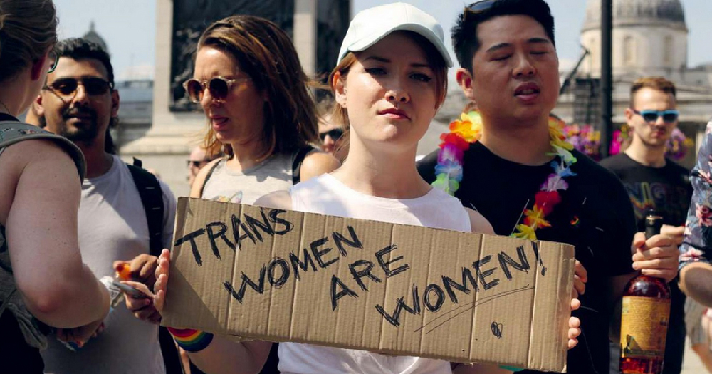 LGB Alliance Ireland group. Feminine person holds placard reading 'Trans women are women'
