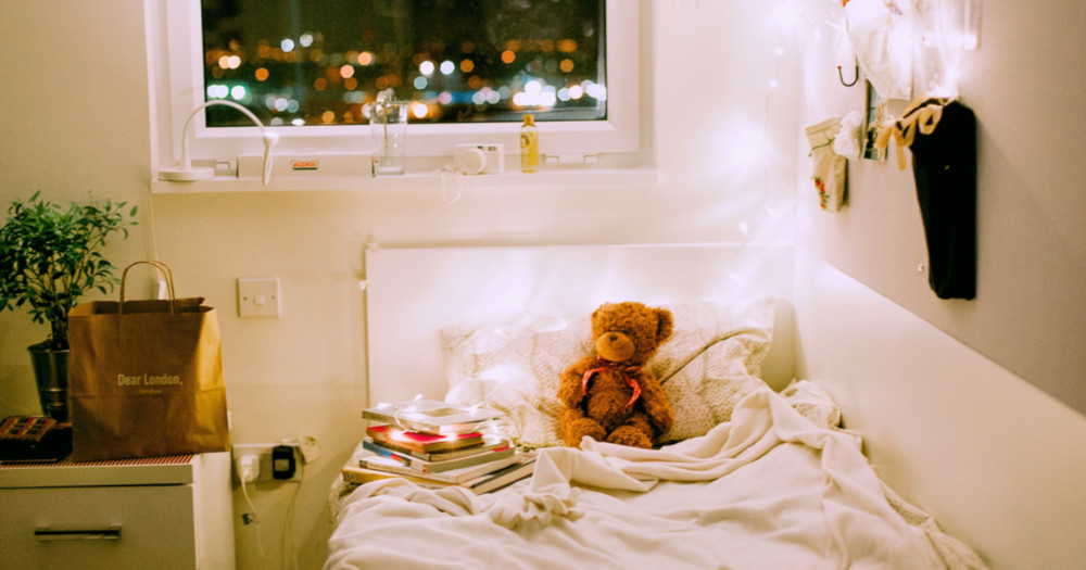 Cozy bedroom with fairy lights, books, and a teddy bear