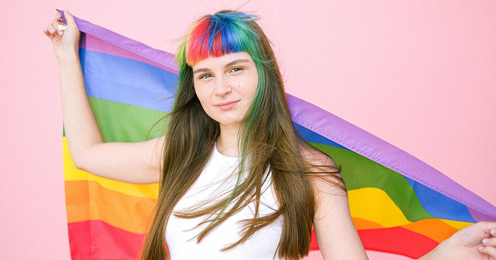 UK census feminine person with rainbow fringe holds a rainbow flag