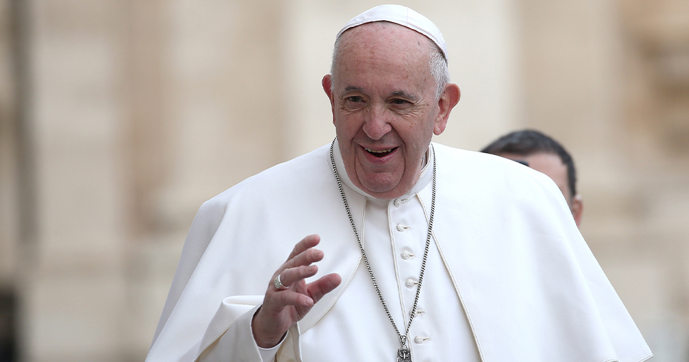 A man in Pope's robes waves his hand