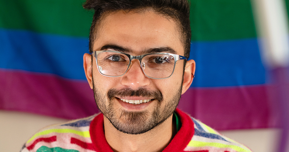 A young man with glasses smiling, behind him a Pride flag. Diego Caixeta from MPOWER talks about addressing the shame around sex.