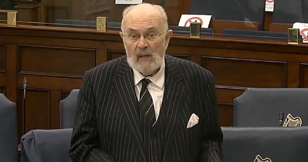 An older man in a suit makes a speech