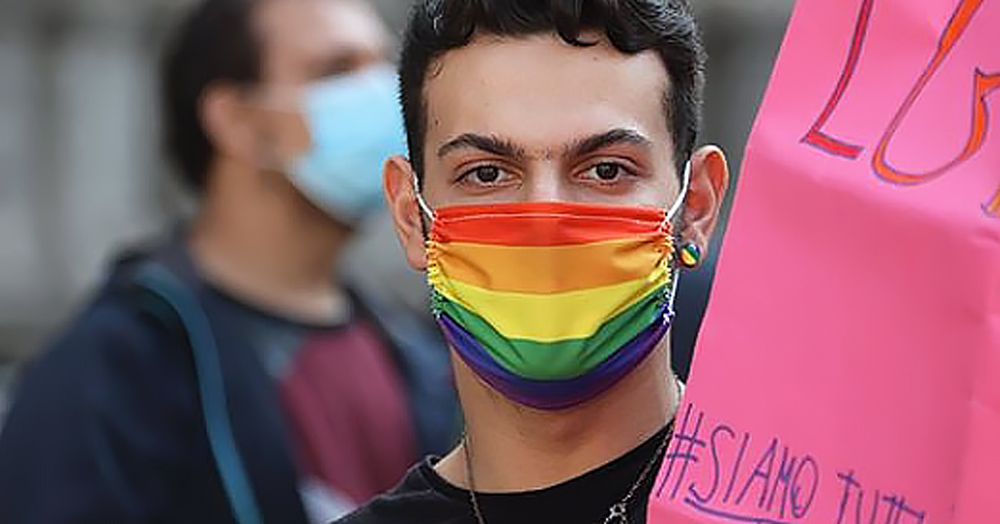 A person wearing a rainbow mask, lawmakers in Italy have recently passed hate crime legislation into next stage