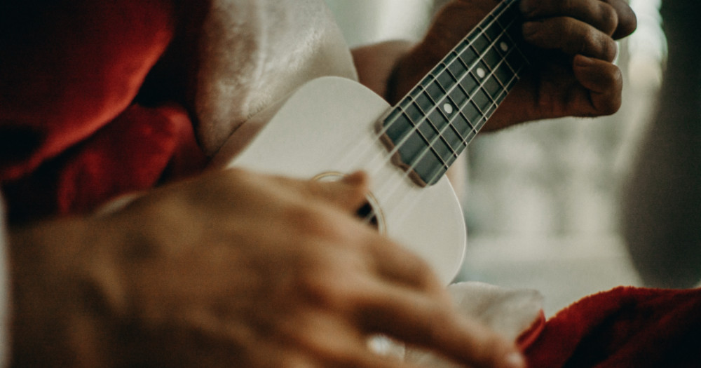 Queer Christmas songs: white ukulele next to a santa suit