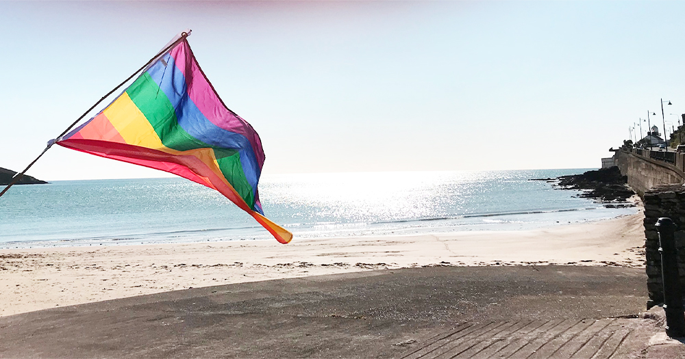 A rainbow flag blowing on a beach