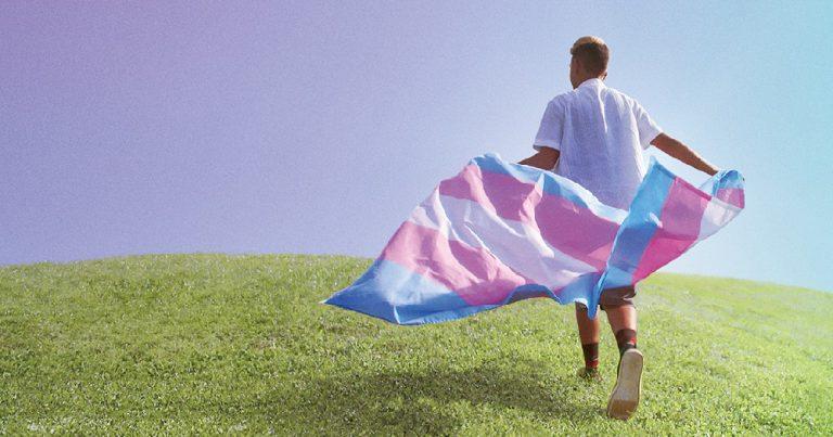 A young man runs through a field carrying a trans flag