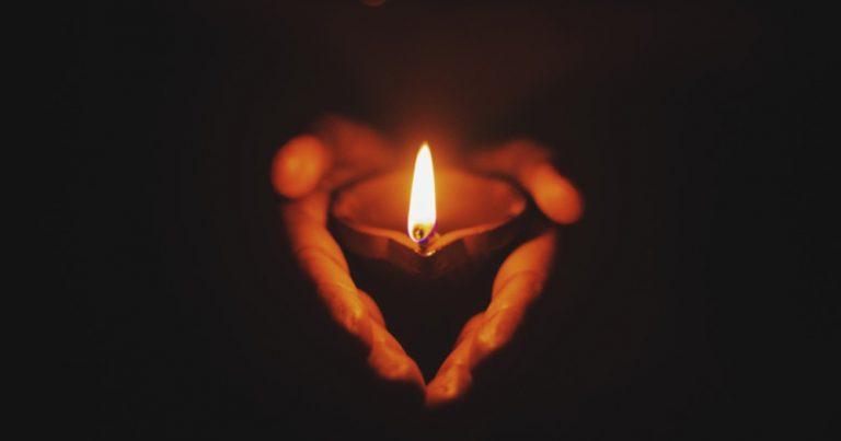 two hands holding a lit candle, transgender lives lost