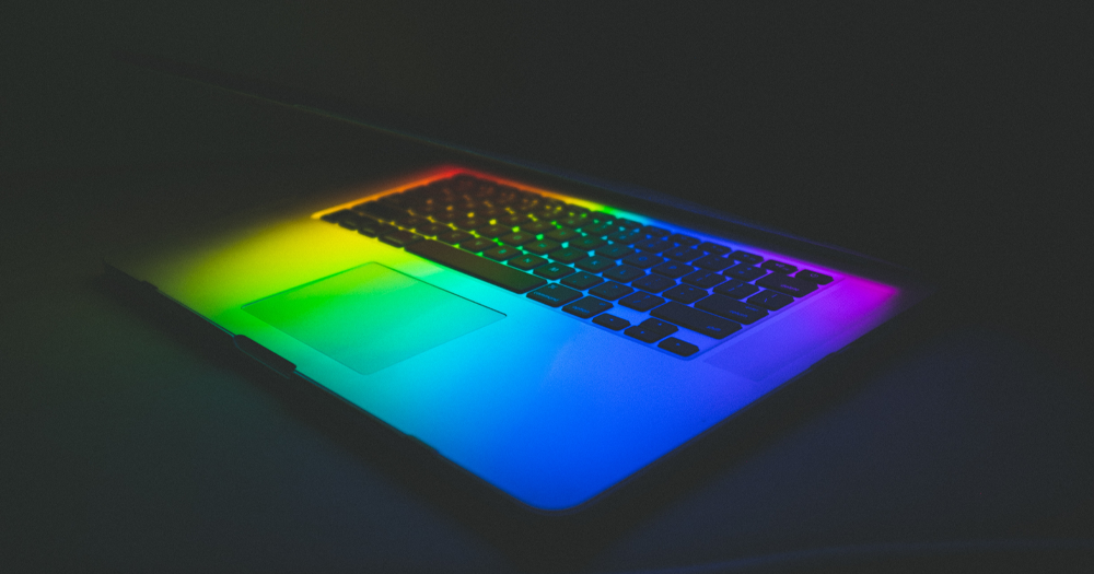 half open online computer with LGBTQ+ community flag colours on the keyboard