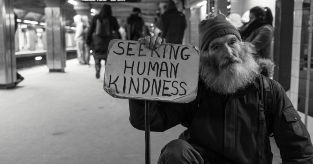 "a homeless man holding a sign that says ""seeking human kindness"", the world is getting kinder."
