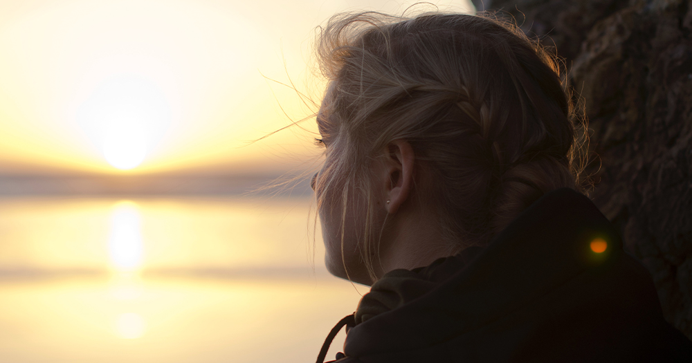 A woman looking toward the sunrise