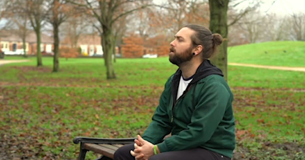 A young man with long hair sits on a park bench